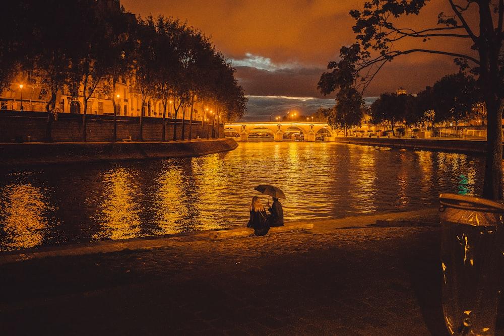 person sitting near pond