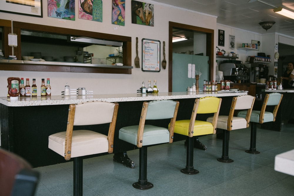 assorted-color barstools in front of table