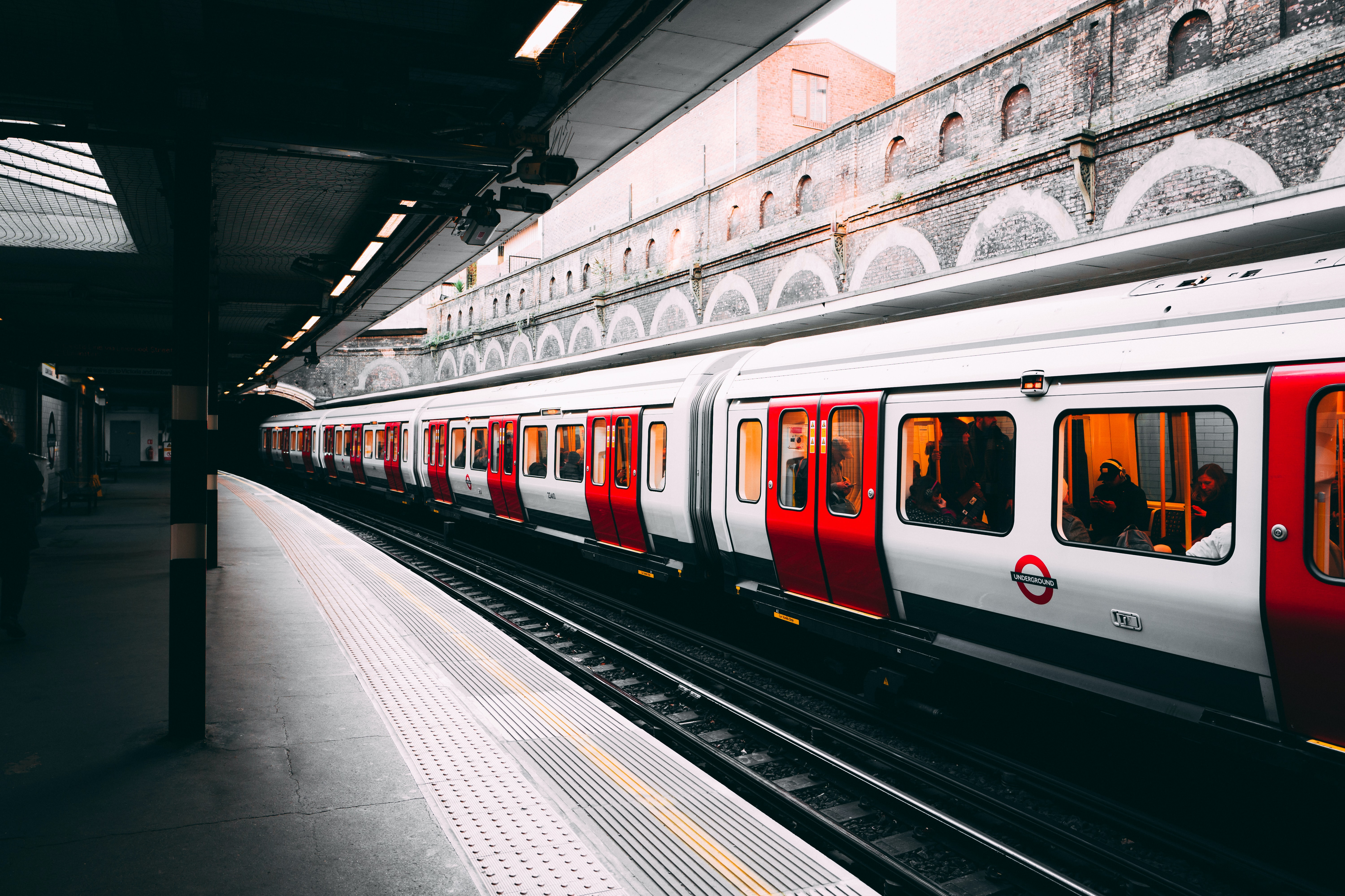 white and red train beside building at daytime