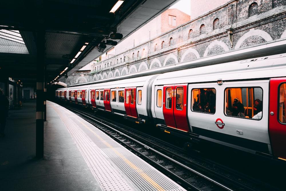 昼間の建物の横にある白と赤の電車
