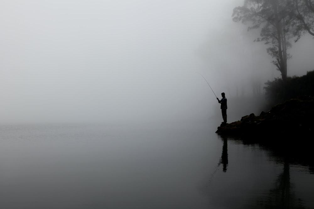 man fishing on calm water behind tree