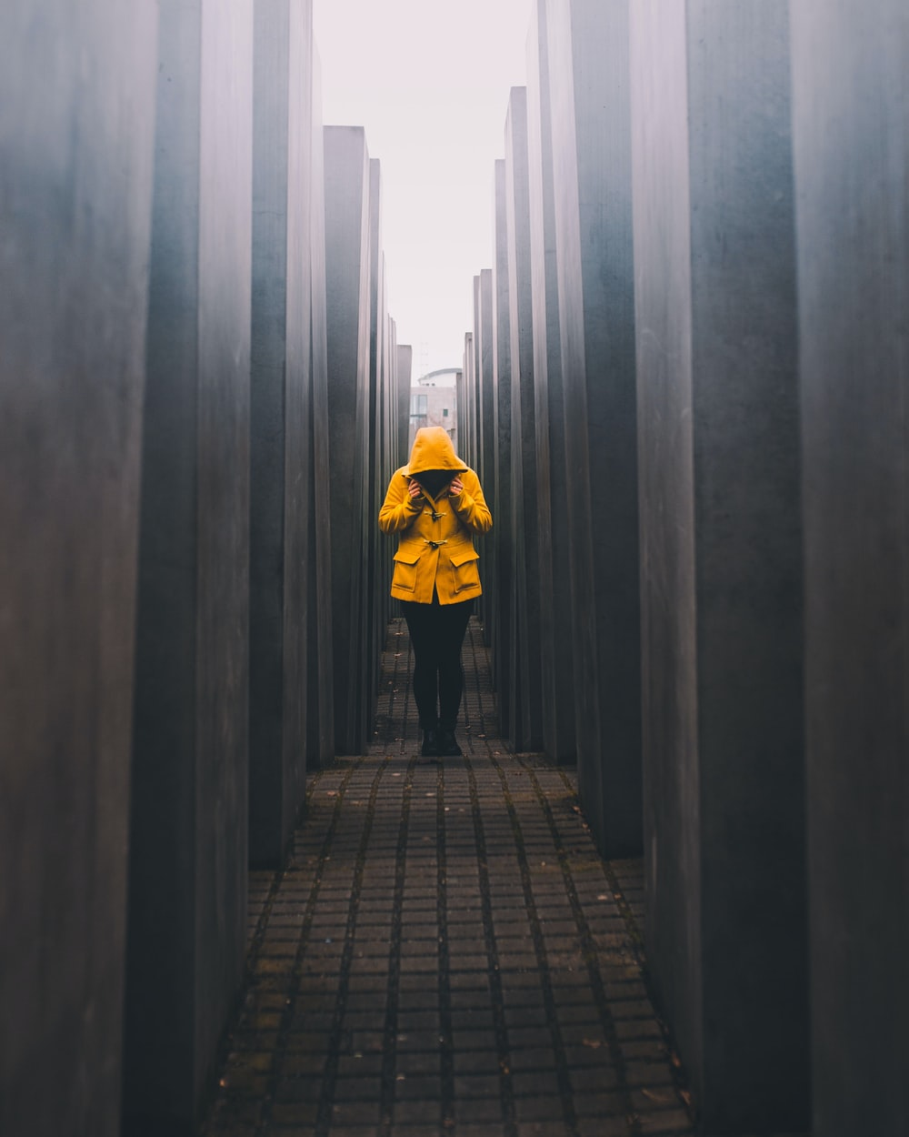 person in mustard hoodie and black pants standing on pathway
