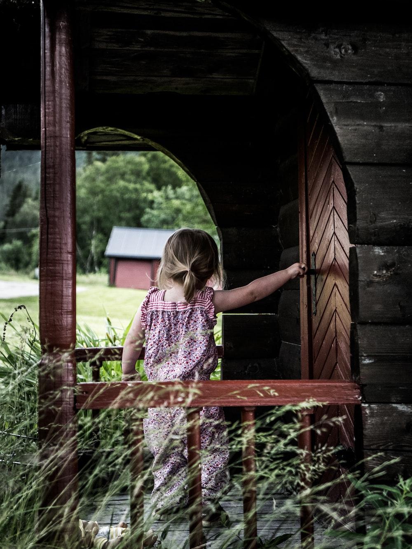 girl in purple dress holding door lever