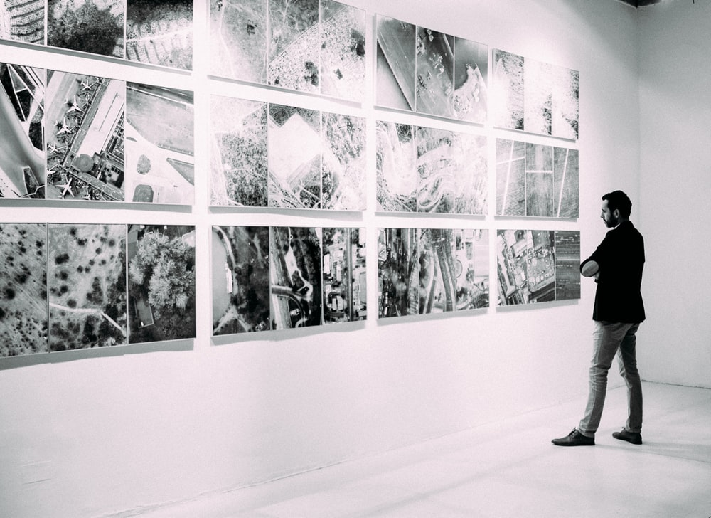 person looking at gallery art pieces on wall