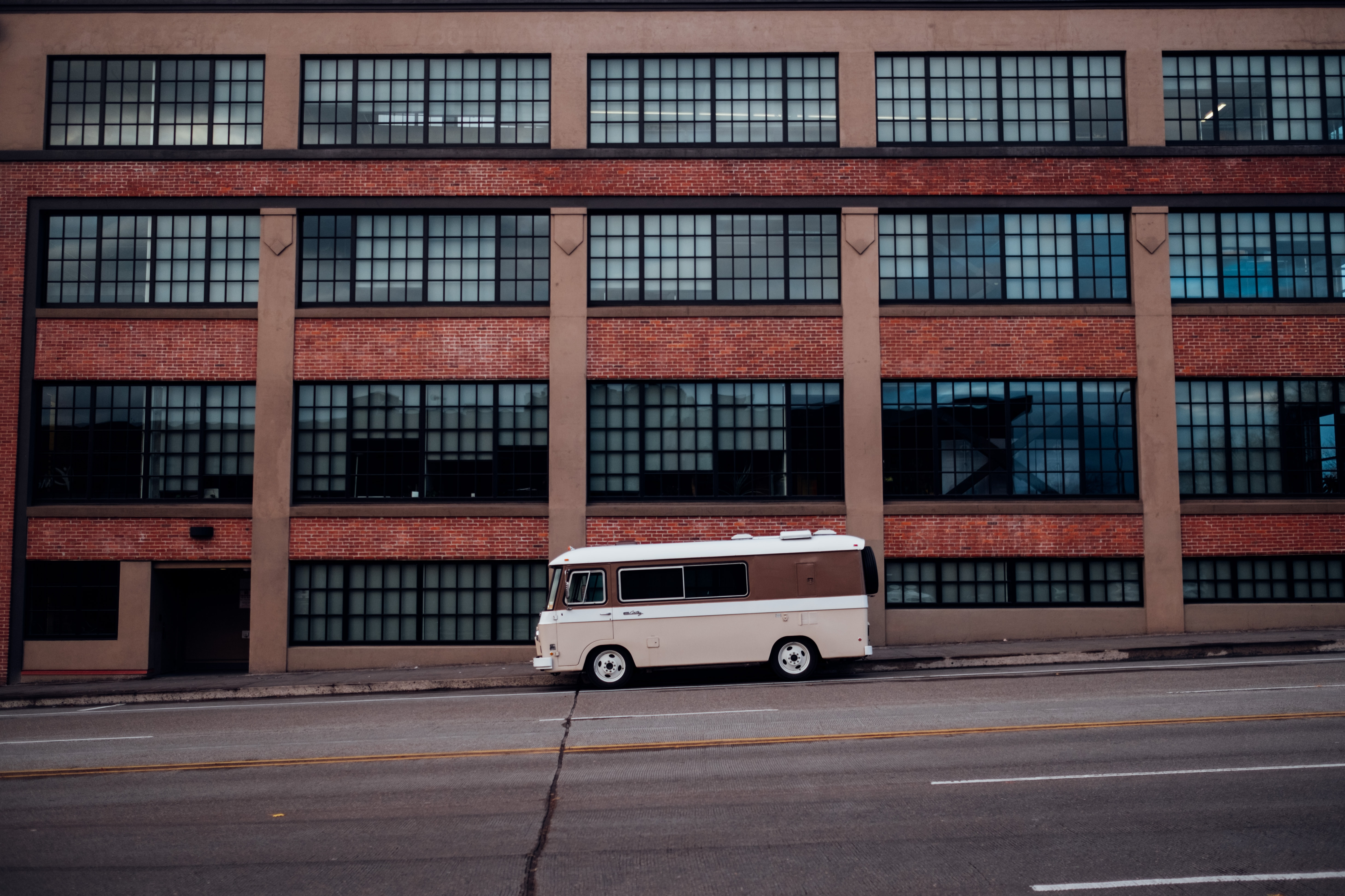 white and brown van in front of brown concrete building