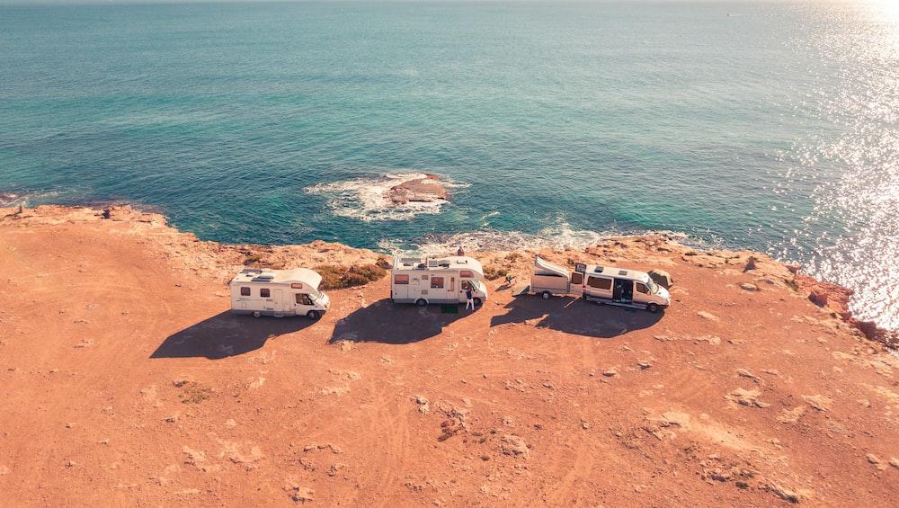 three white RV parks near sea at daytime
