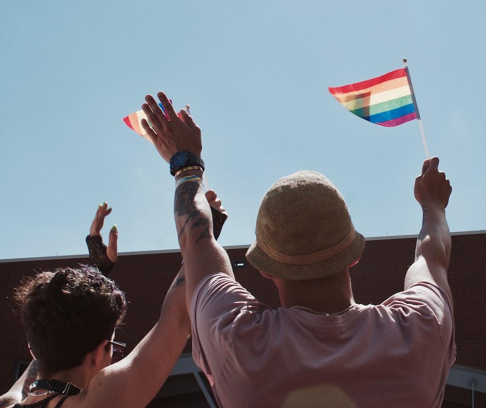 man holding flag while raising hands