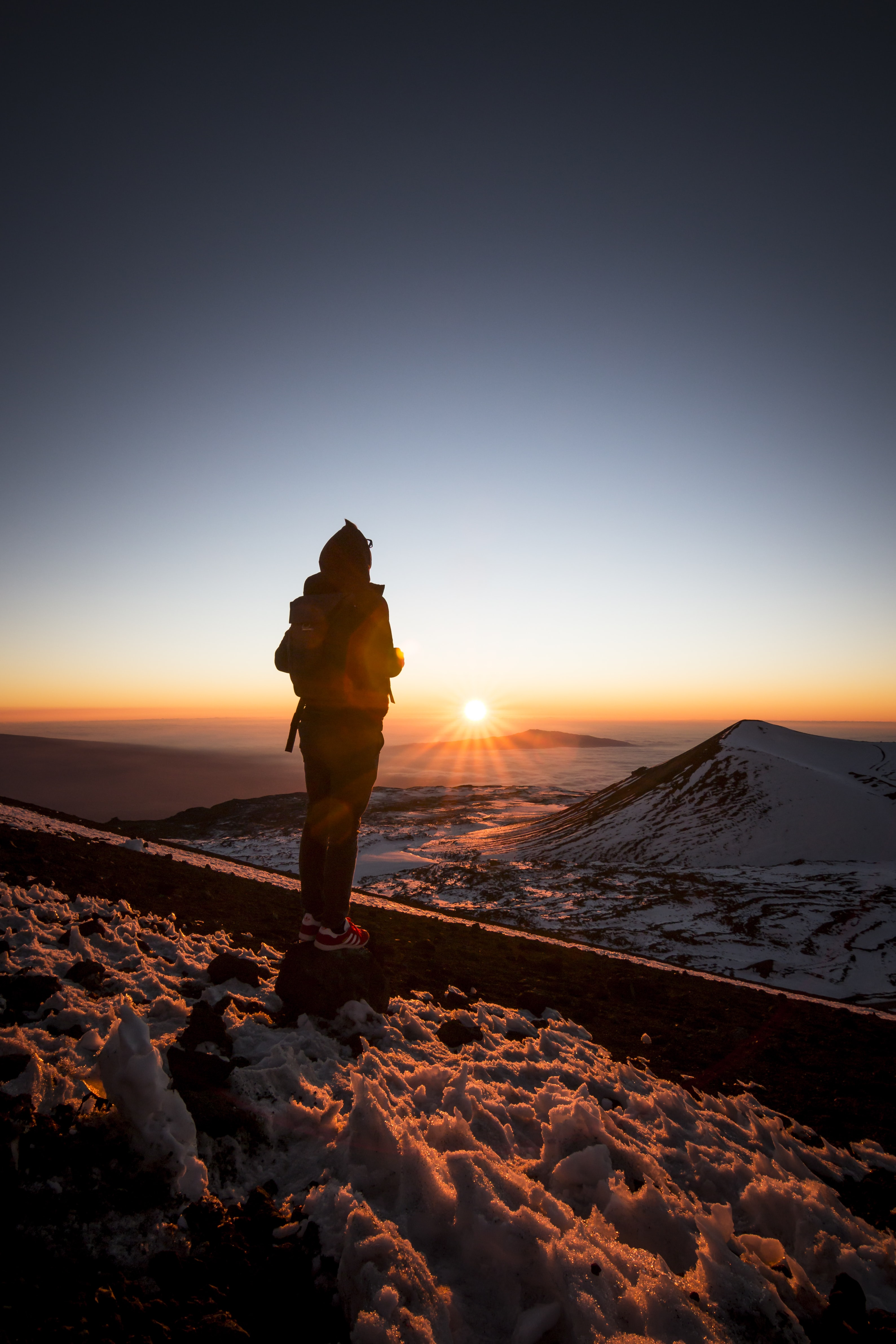 person carrying bag standing on snow coated ground looking at sun