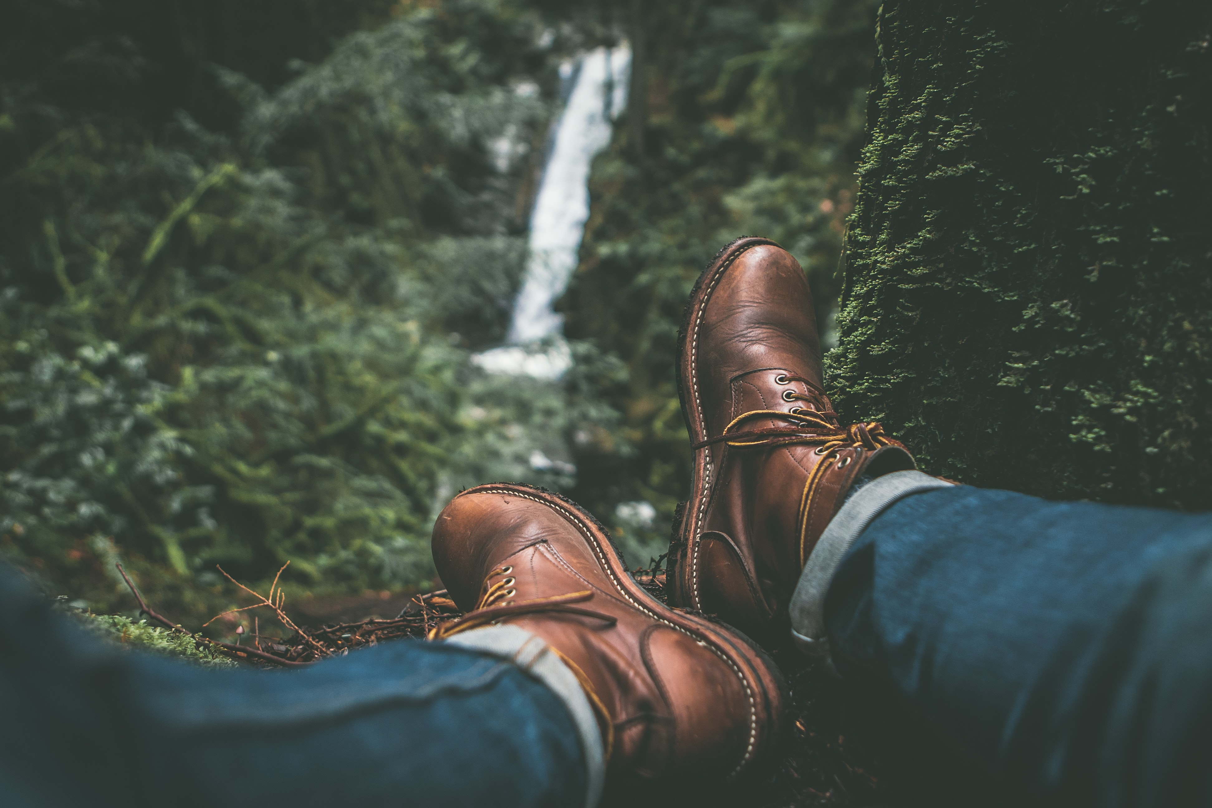 person wearing brown leather boots near green leafed plants