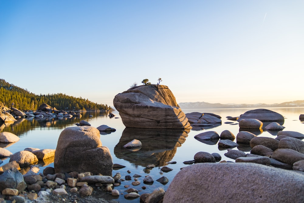 brown rock formation beside calm body of water near mountain at daytime