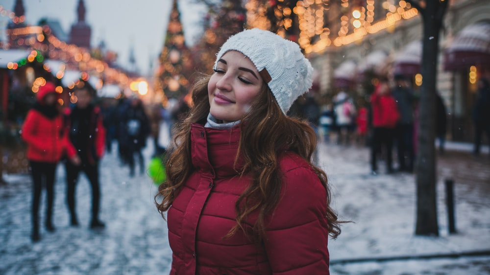 selective focus photography of woman wearing red parka jacket while standing