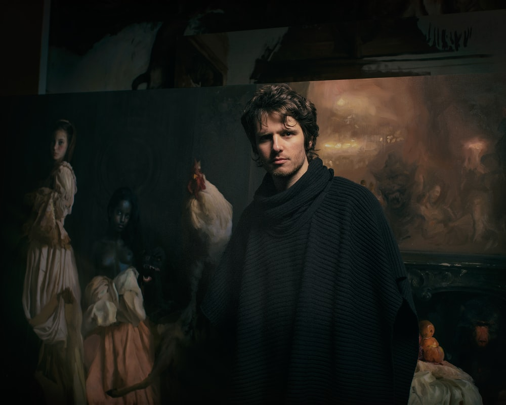 man in black poncho standing in front of paintings