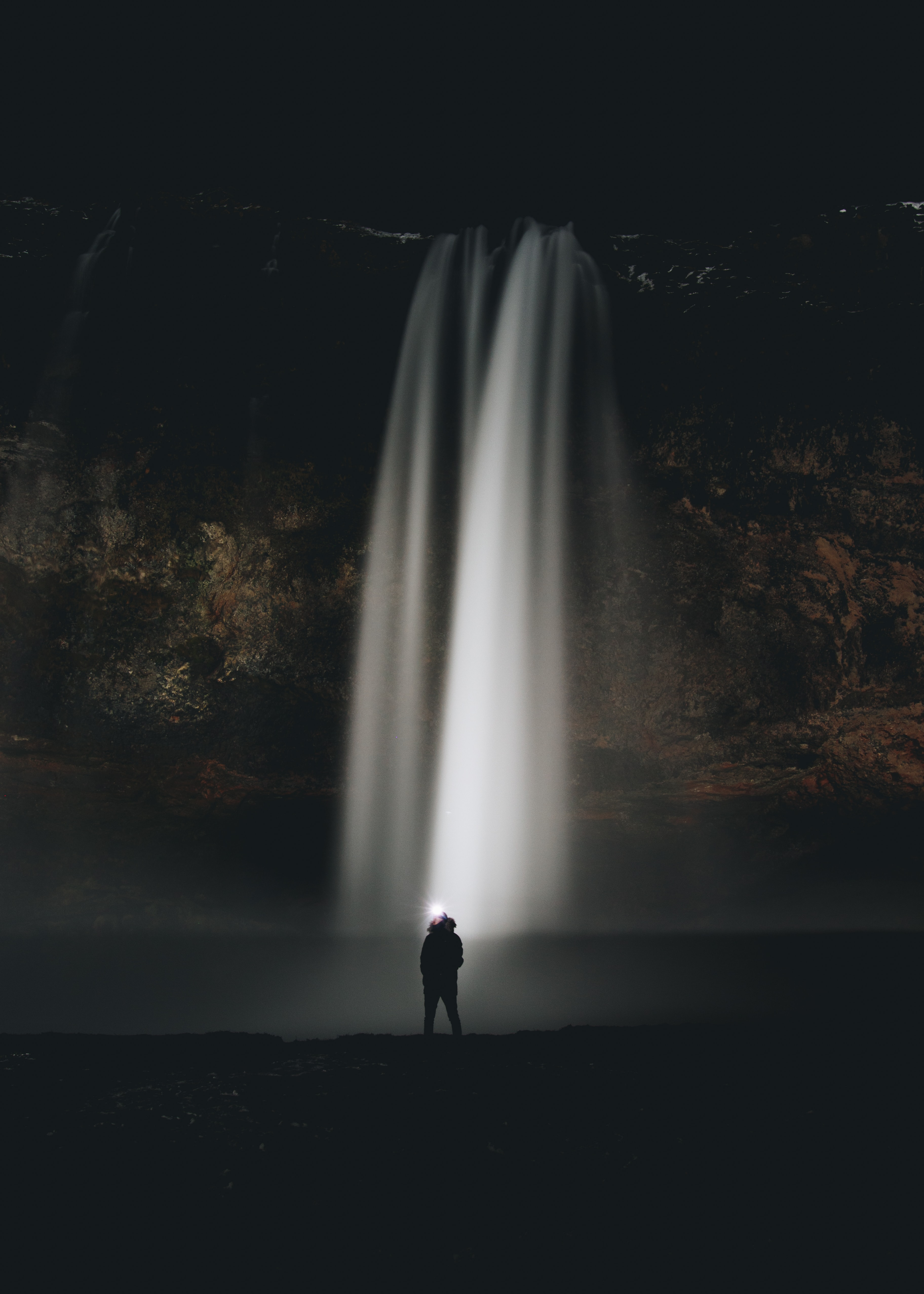 man standing in front of waterfalls during nighttime