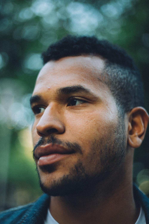 bokeh photography of man wearing blue top