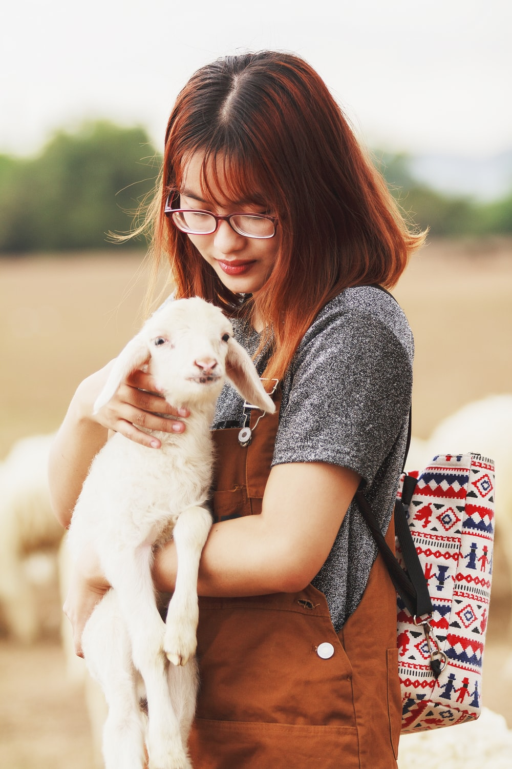 woman carrying a goat