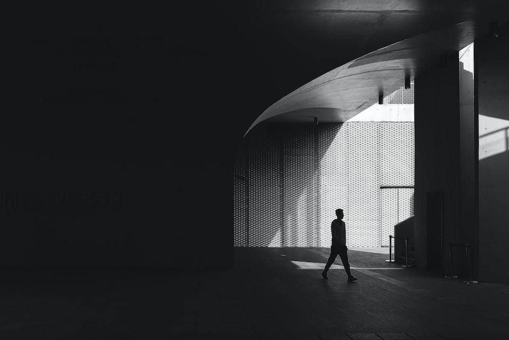 silhouette photography of man walking on floor beside post