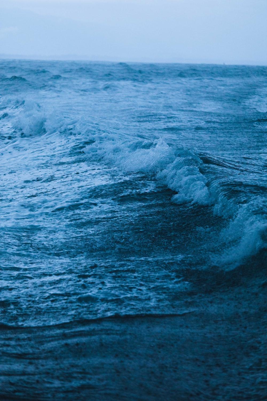 low-angle photography of crashing waves during raining
