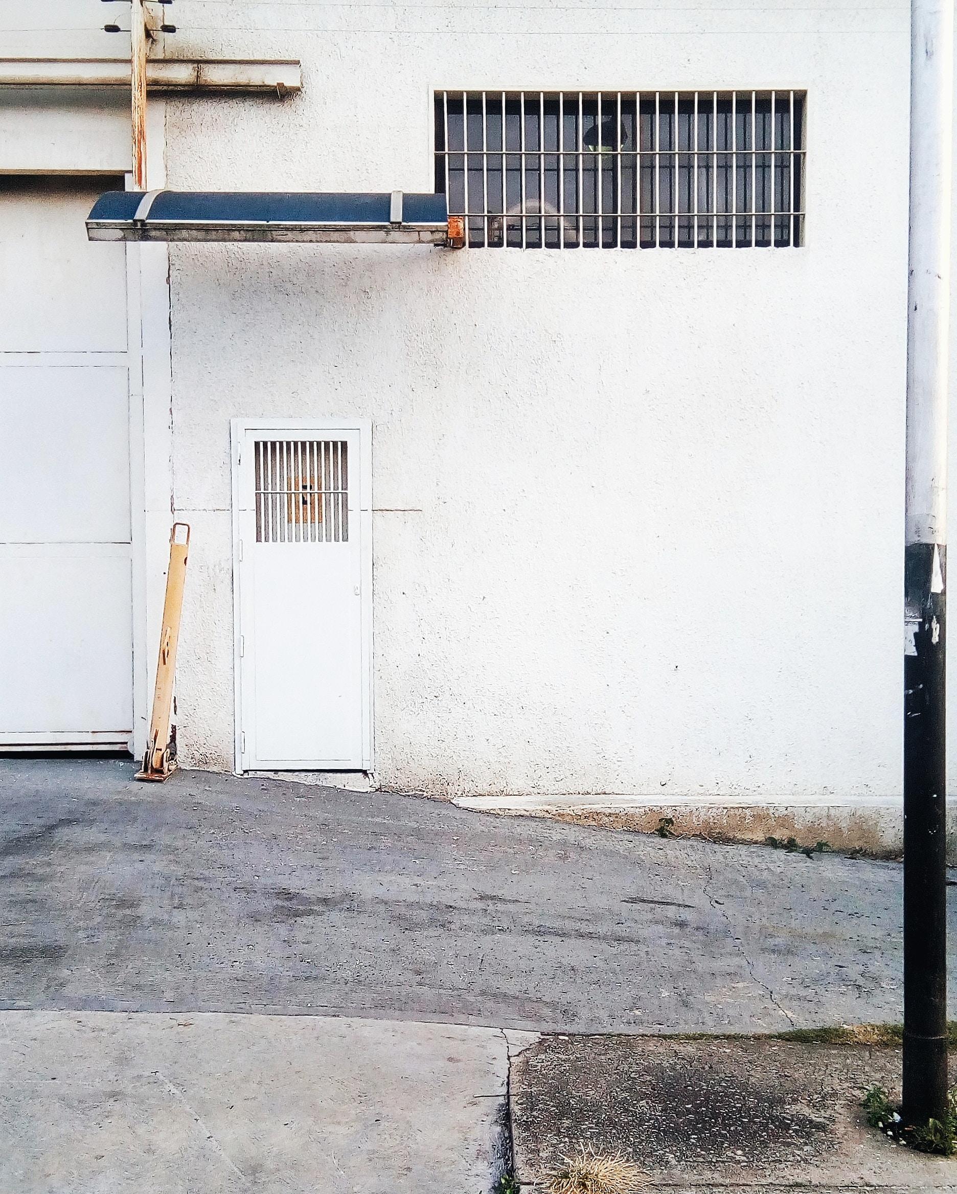 white metal closed door near road at daytime