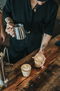 man pouring coffee in glass cups