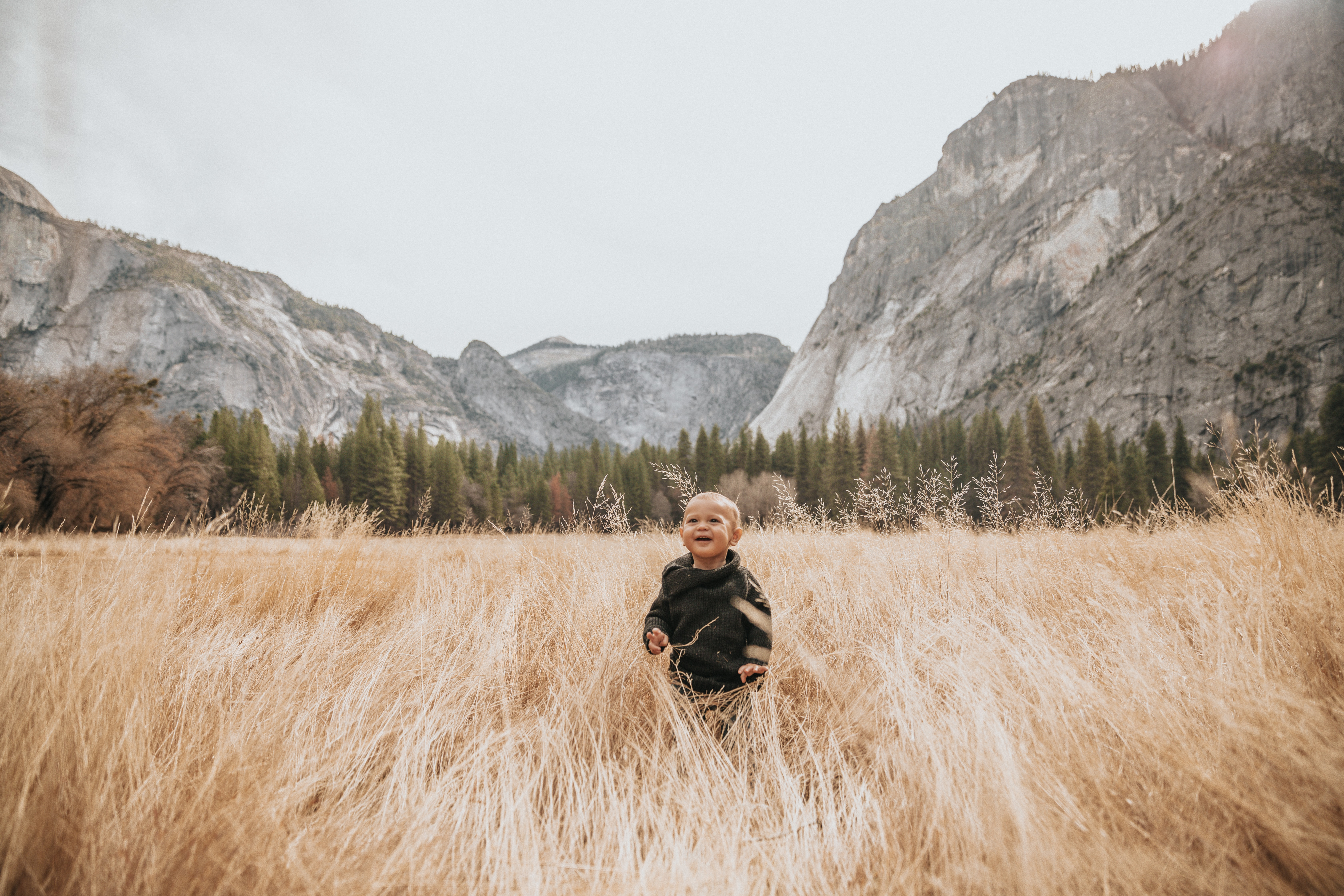 boy in black jacket stand on brown grass near mountain