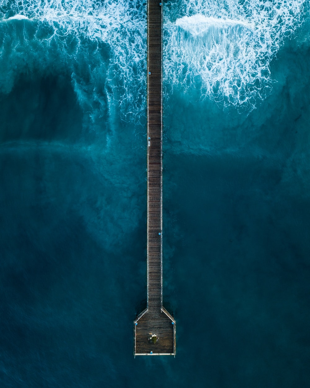 aerial photography of person standing on dock beside sea at daytime