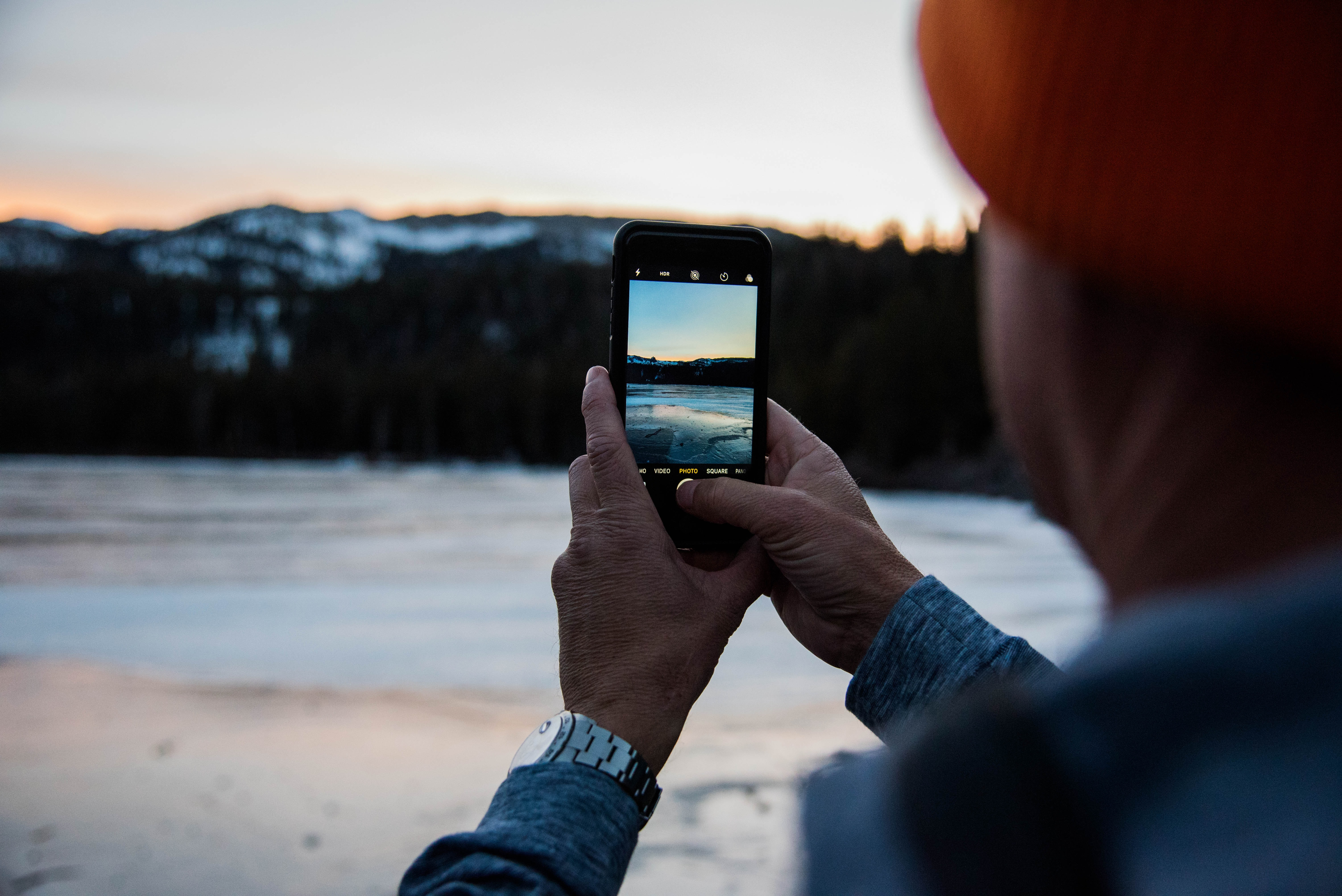 person holding smartphone taking picture of body of water