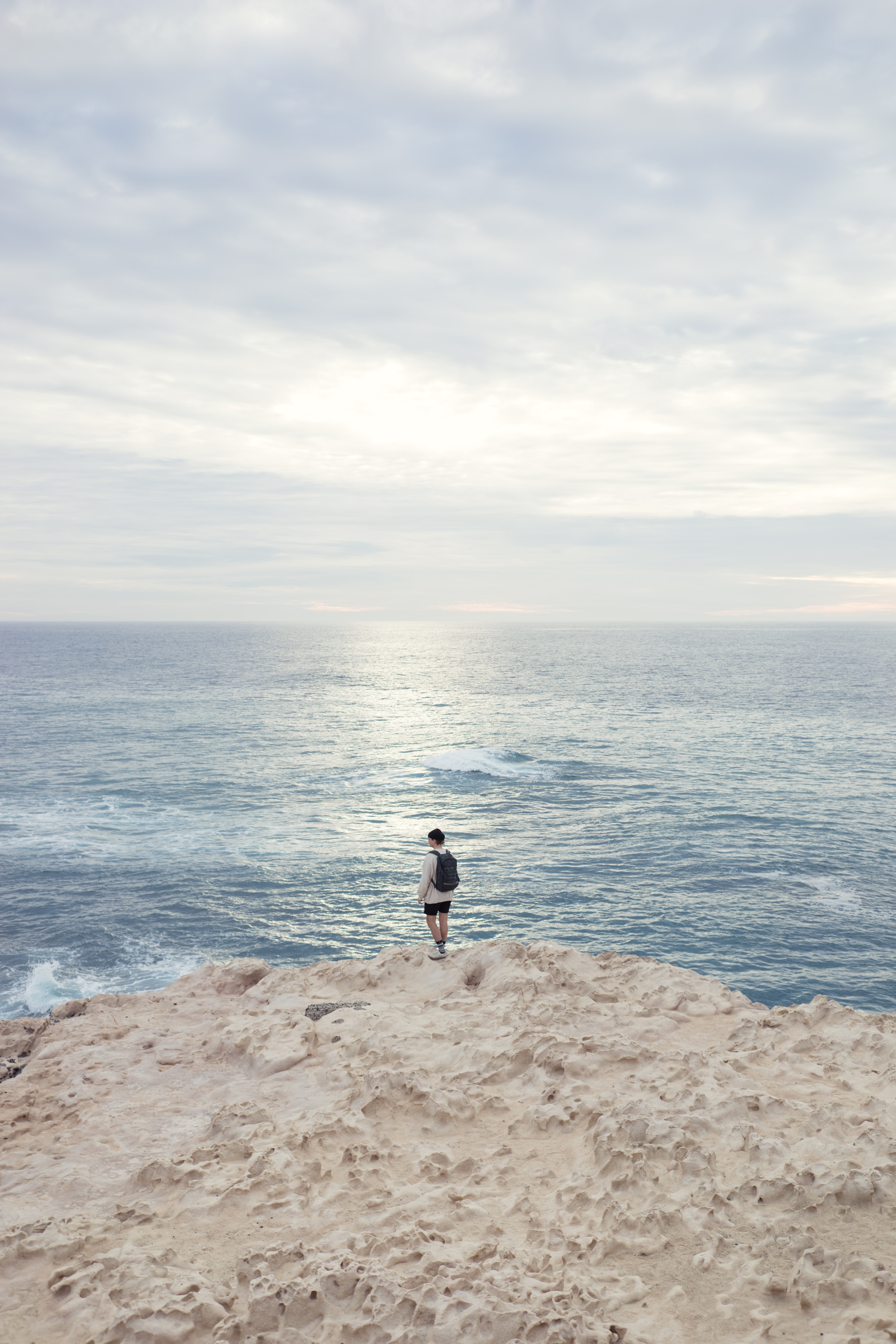 person standing on the edge of the cliff near ocean