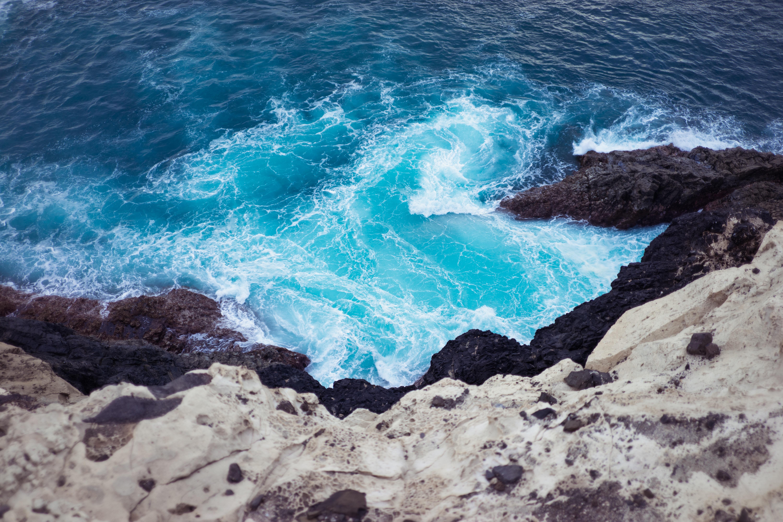 top view photo of ocean waves unto mountain shoreline