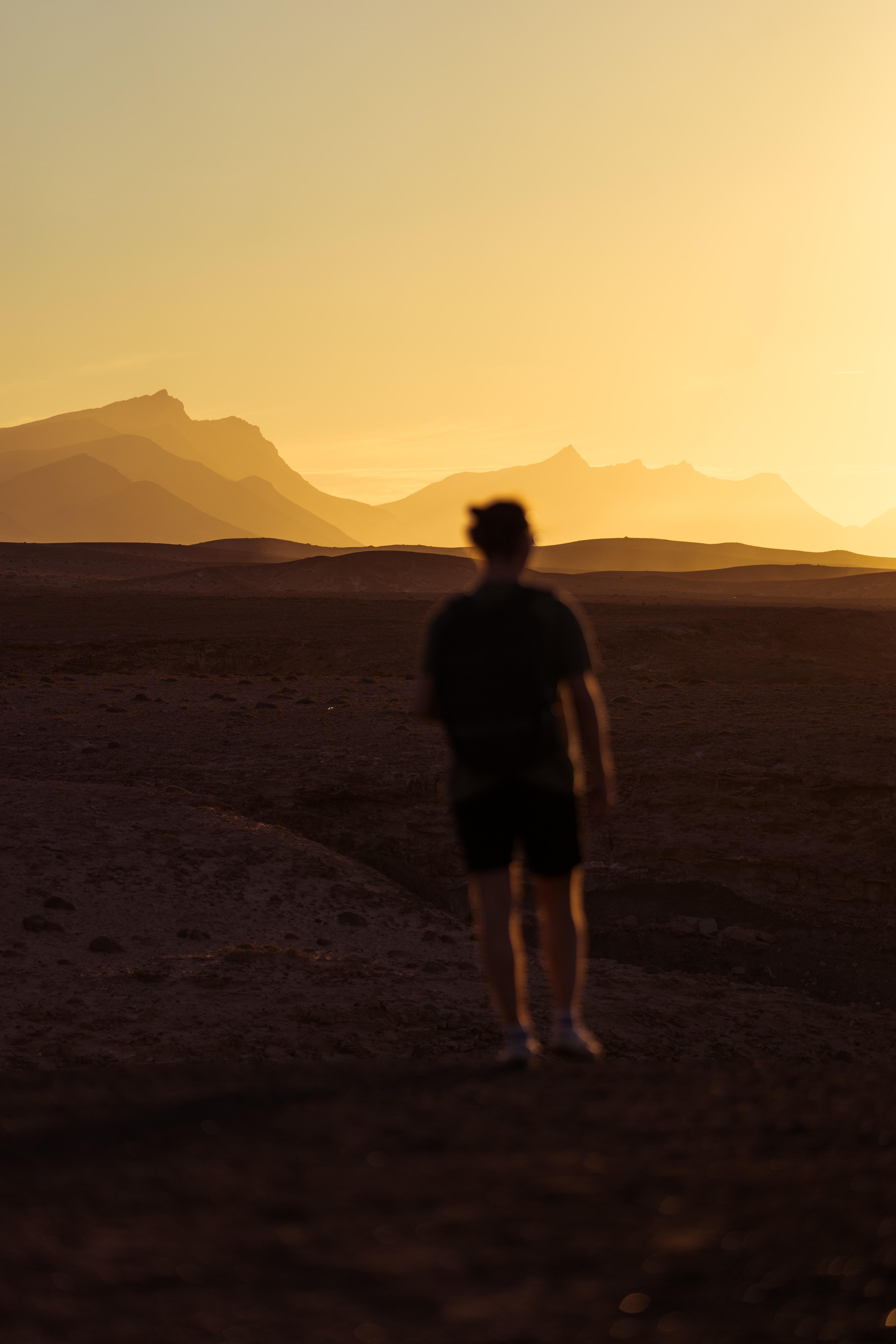 person walking on desert during golden hour