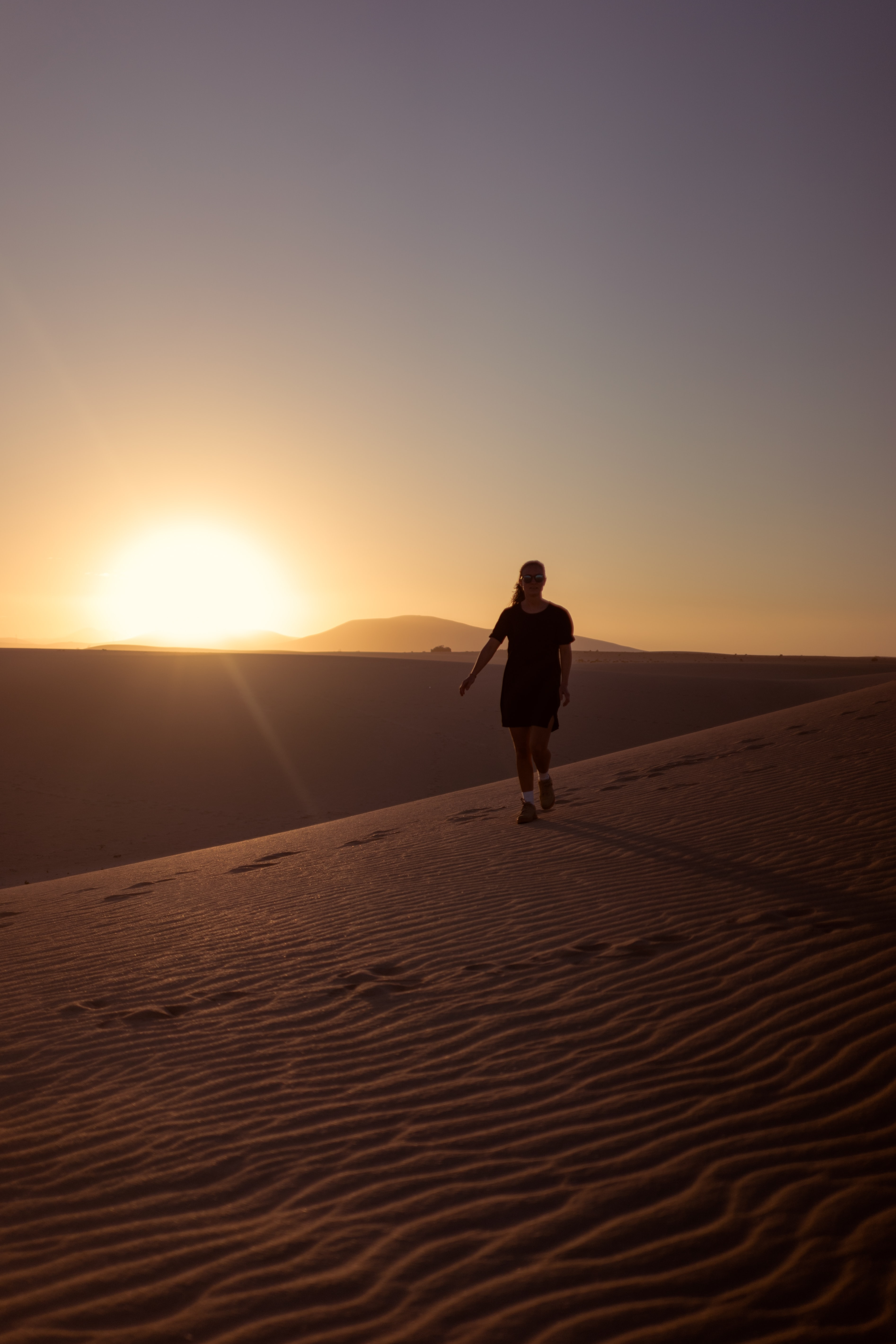 woman walking on desert during sunset