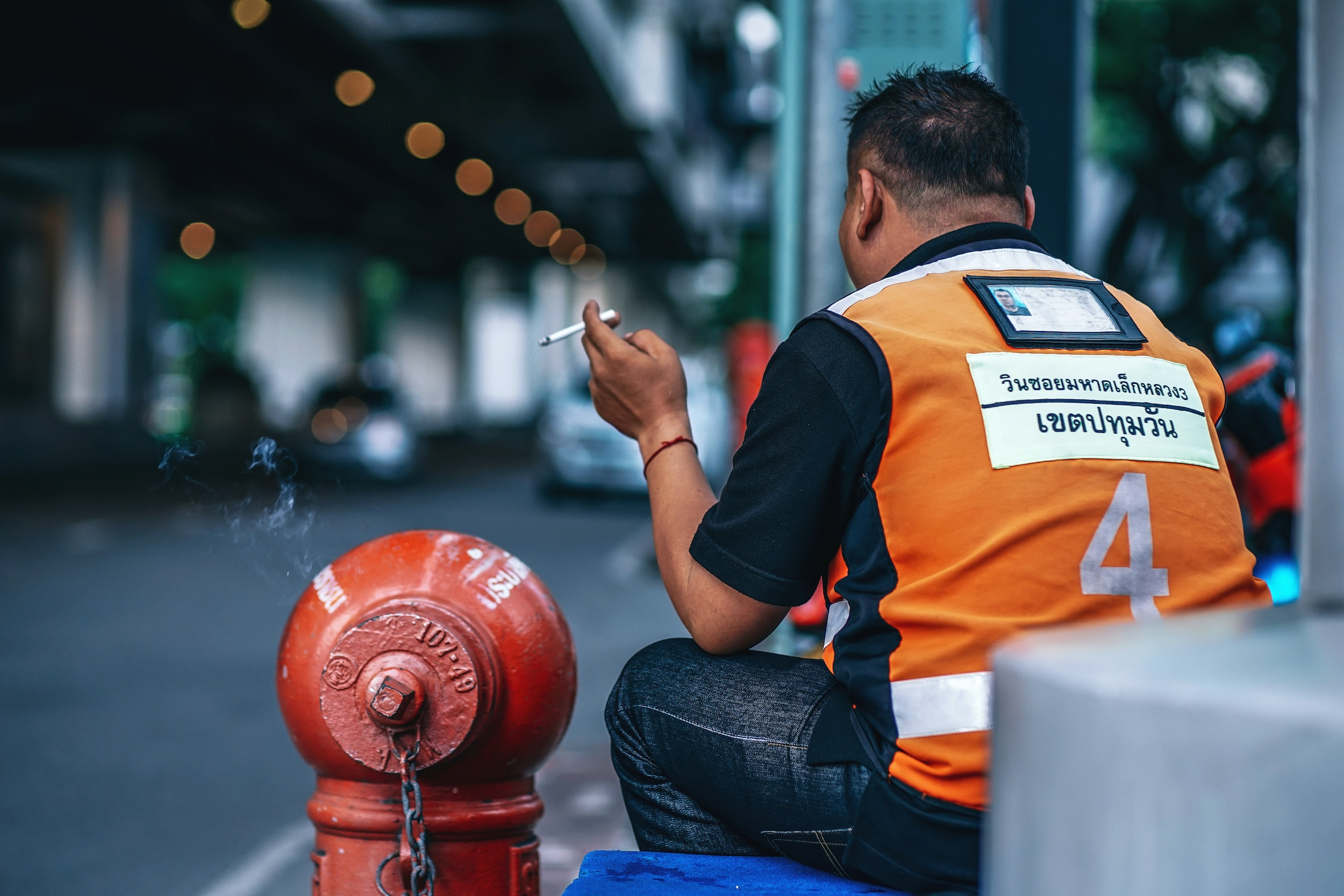 man smoking beside fire hydrant