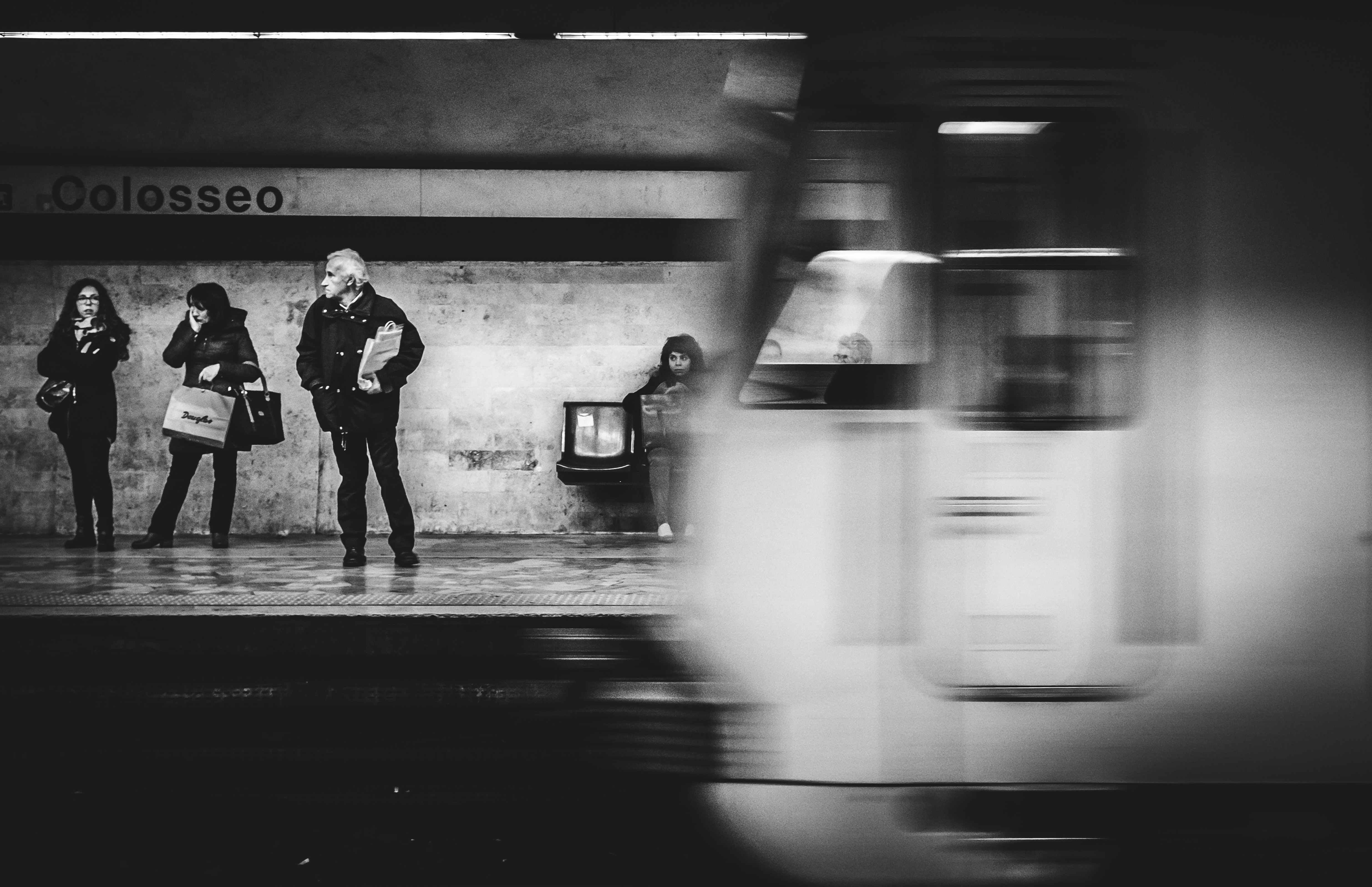 grayscale photo of three people standing on train station