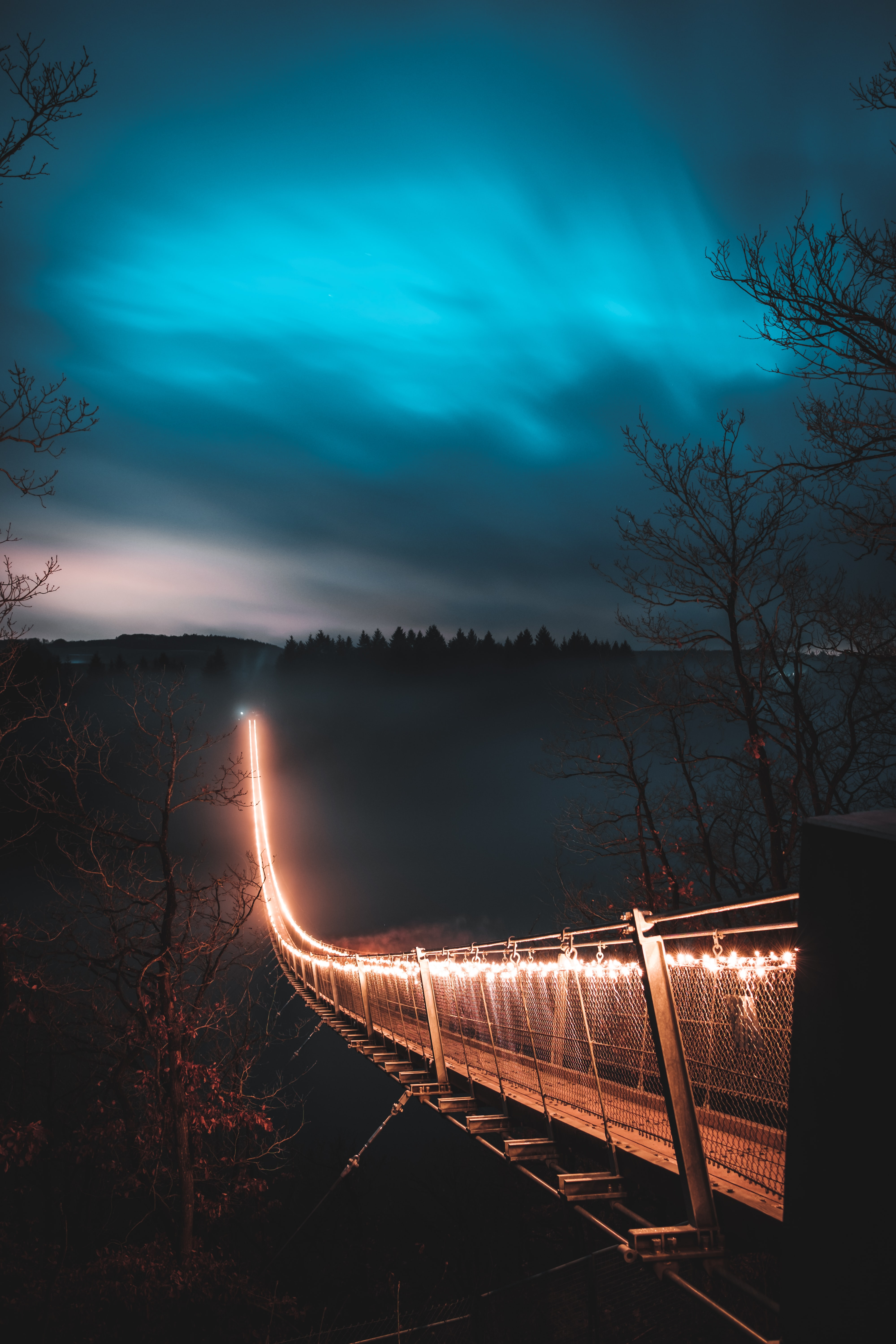 brown suspension bridge with light during nighttime