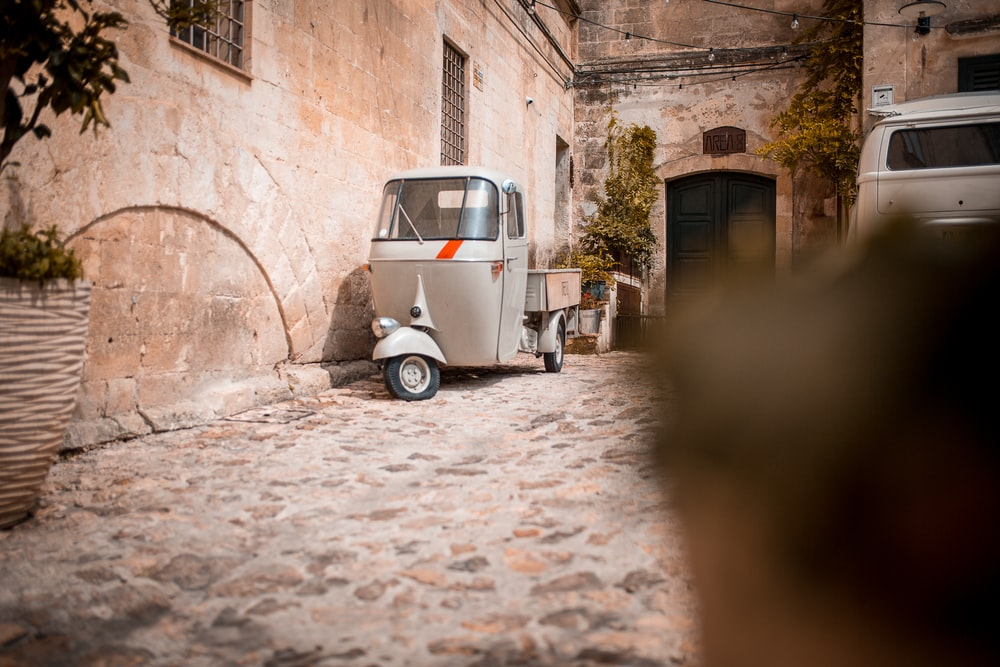 gray auto rickshaw near gray concrete wall