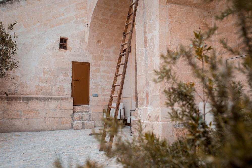 brown wooden ladder beside door
