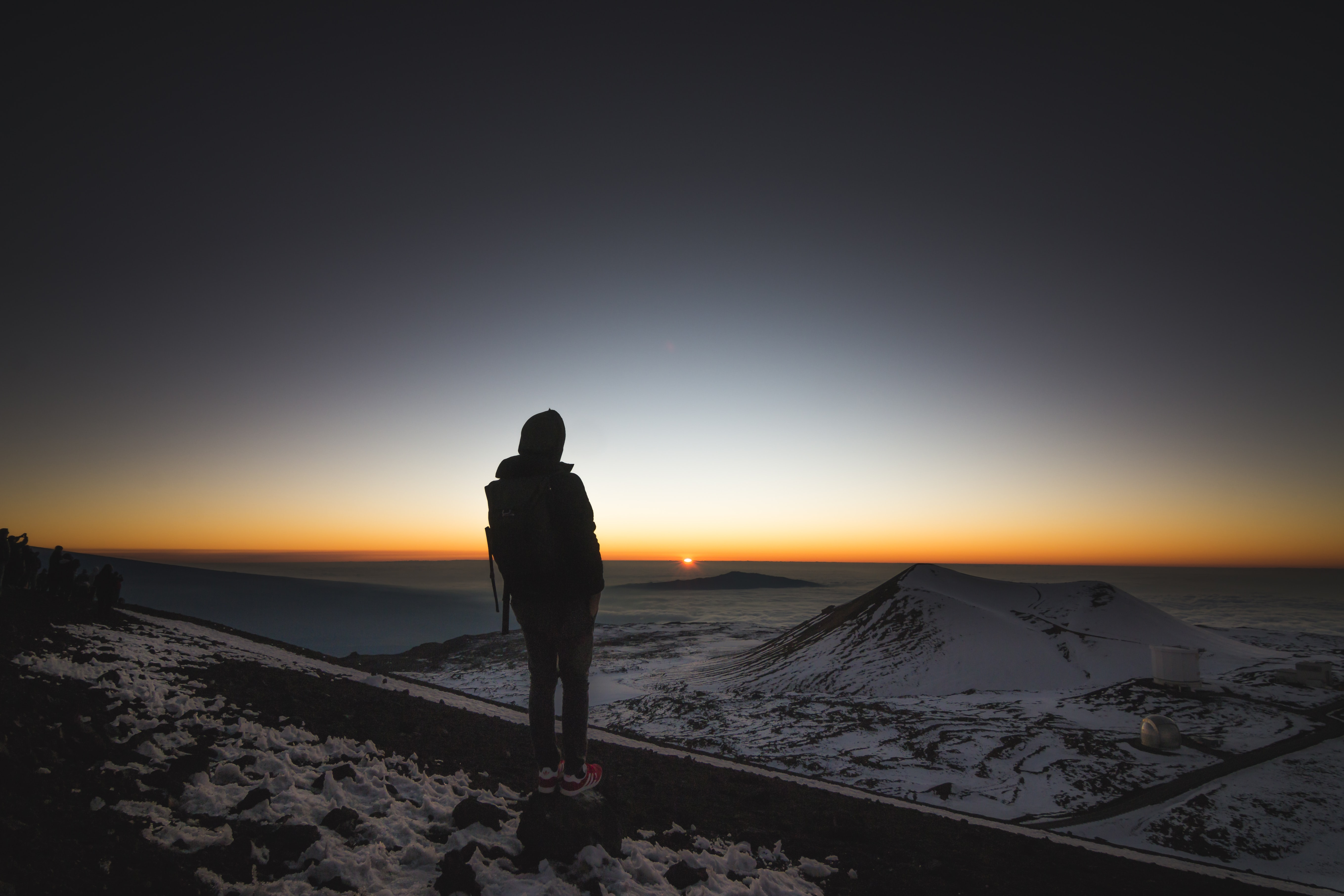 person on top of mountain looking at sunset