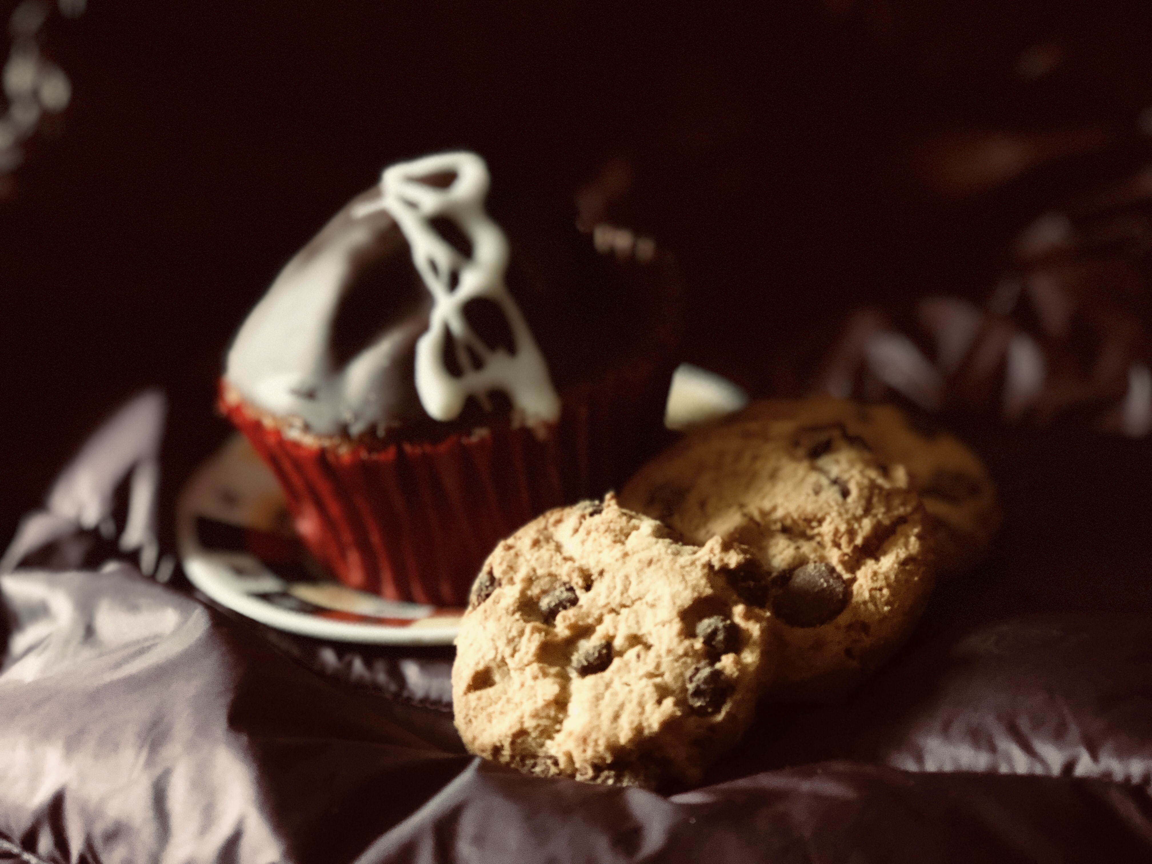 cookies and chocolate muffin on black textile