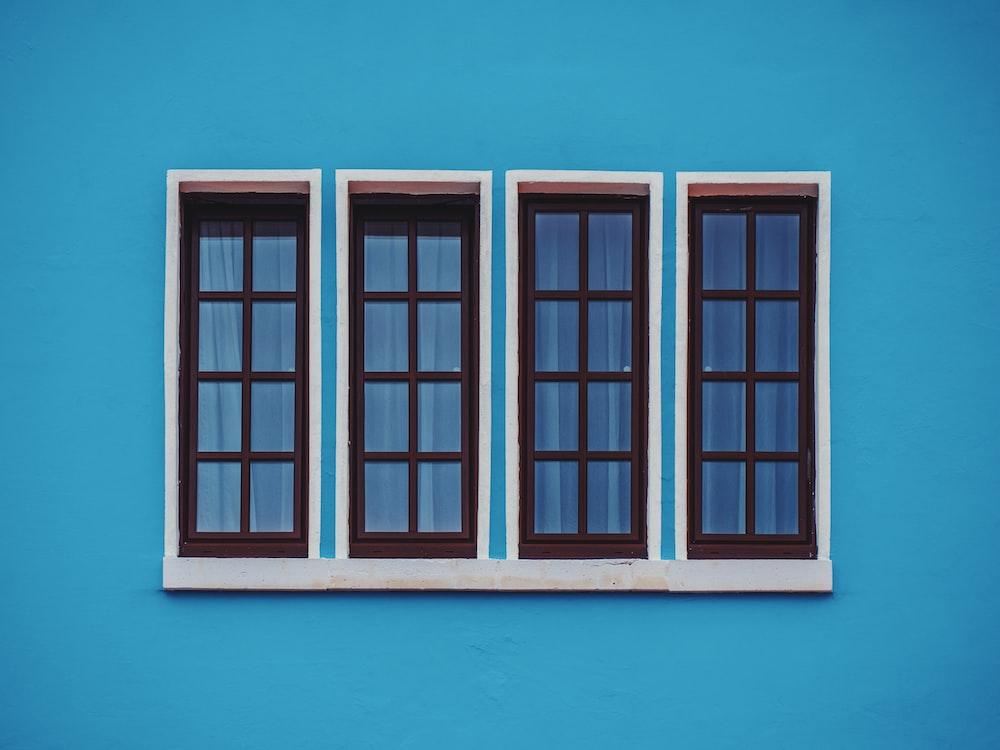 青いコンクリートの壁の透明なガラス窓