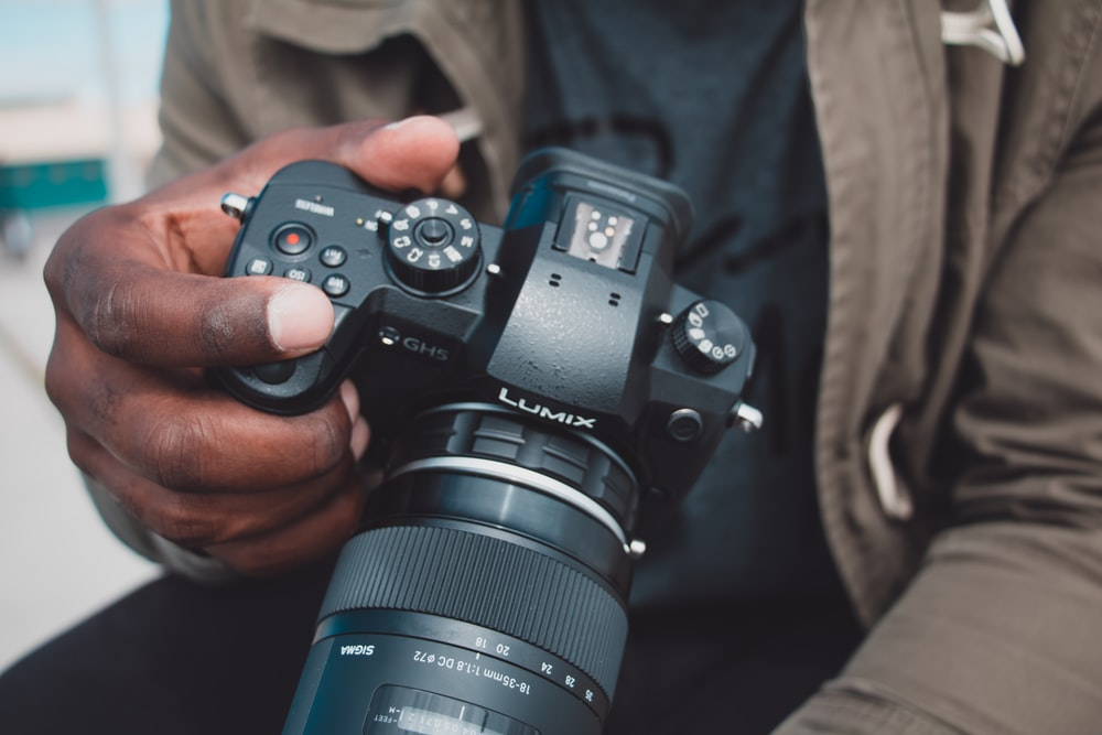 man holding black Lumix DSLR camera