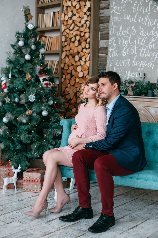 woman and man sitting on sofa beside Christmas tree