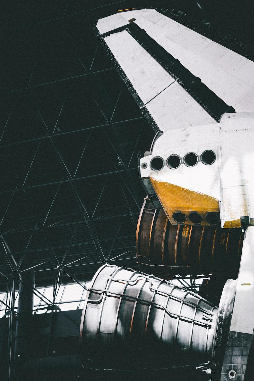 photo of white rocket ship inside warehouse