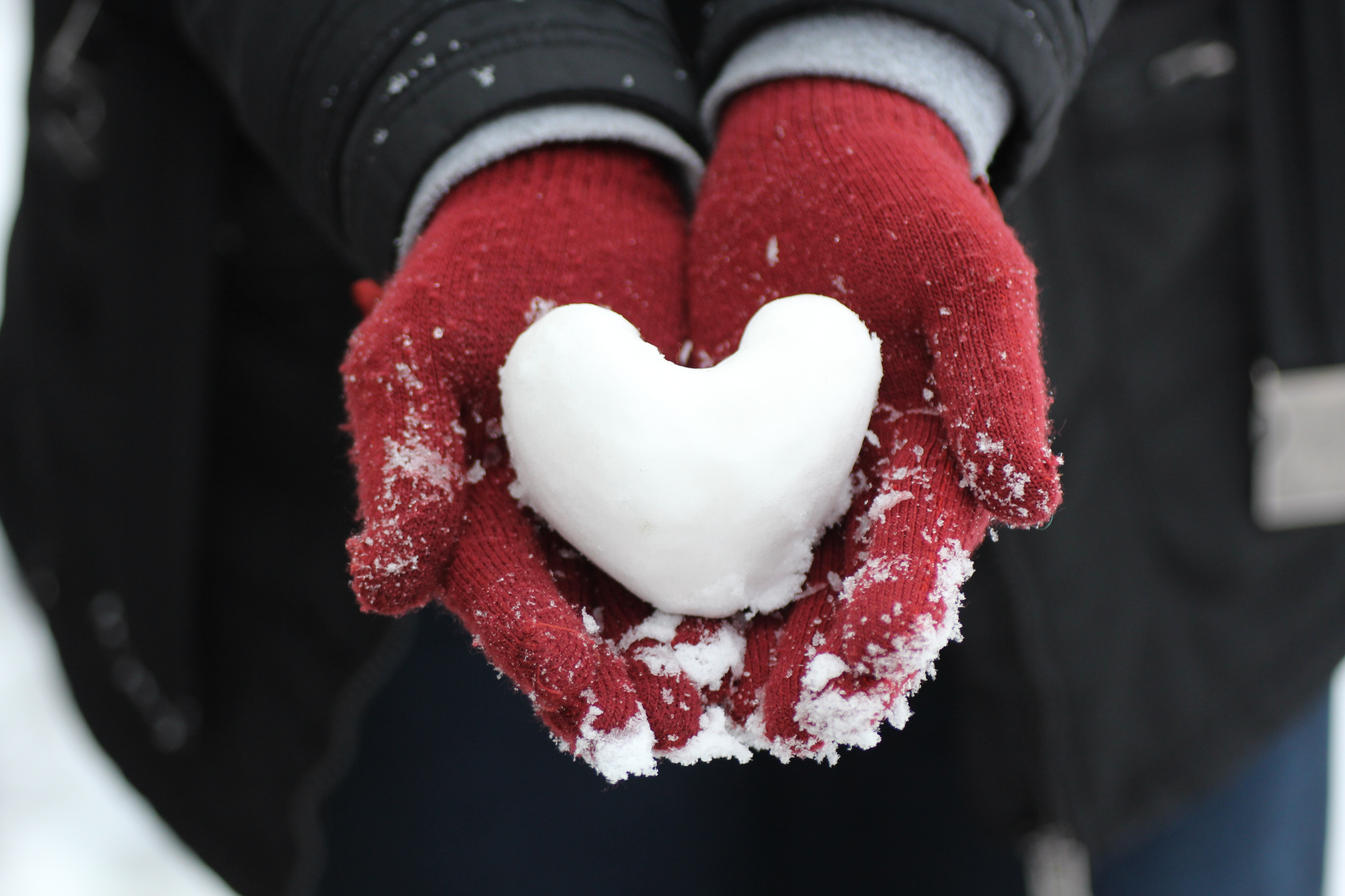 person holding heart-shaped snow