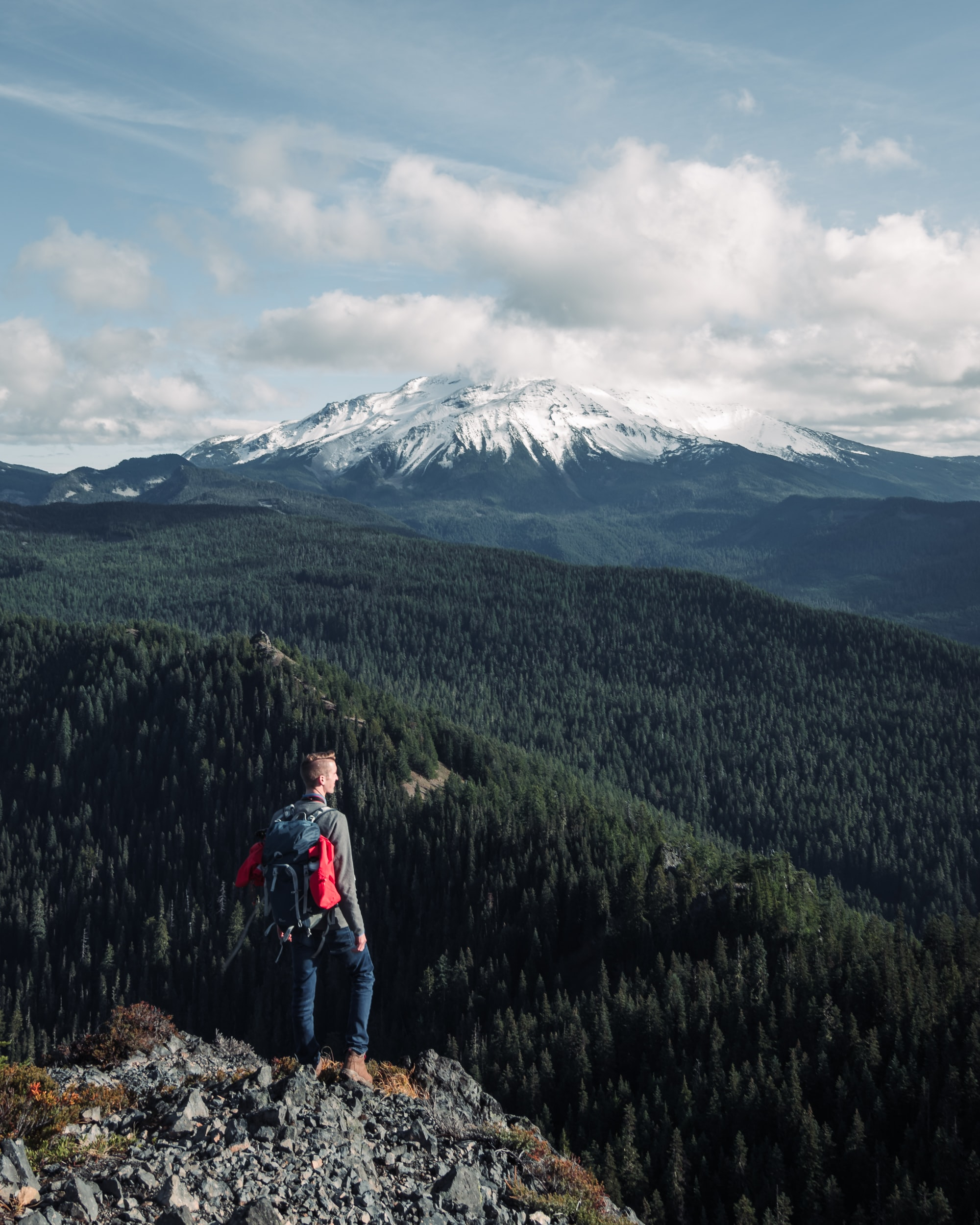 man standing on peak of mountain under cloudy sky