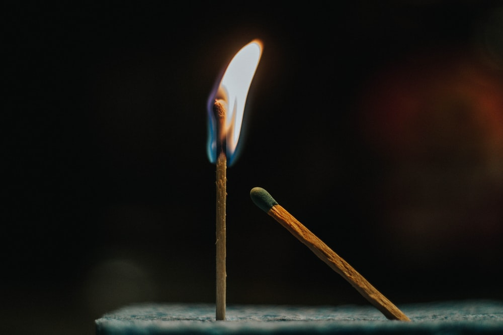 shallow focus photography of lighted matchstick