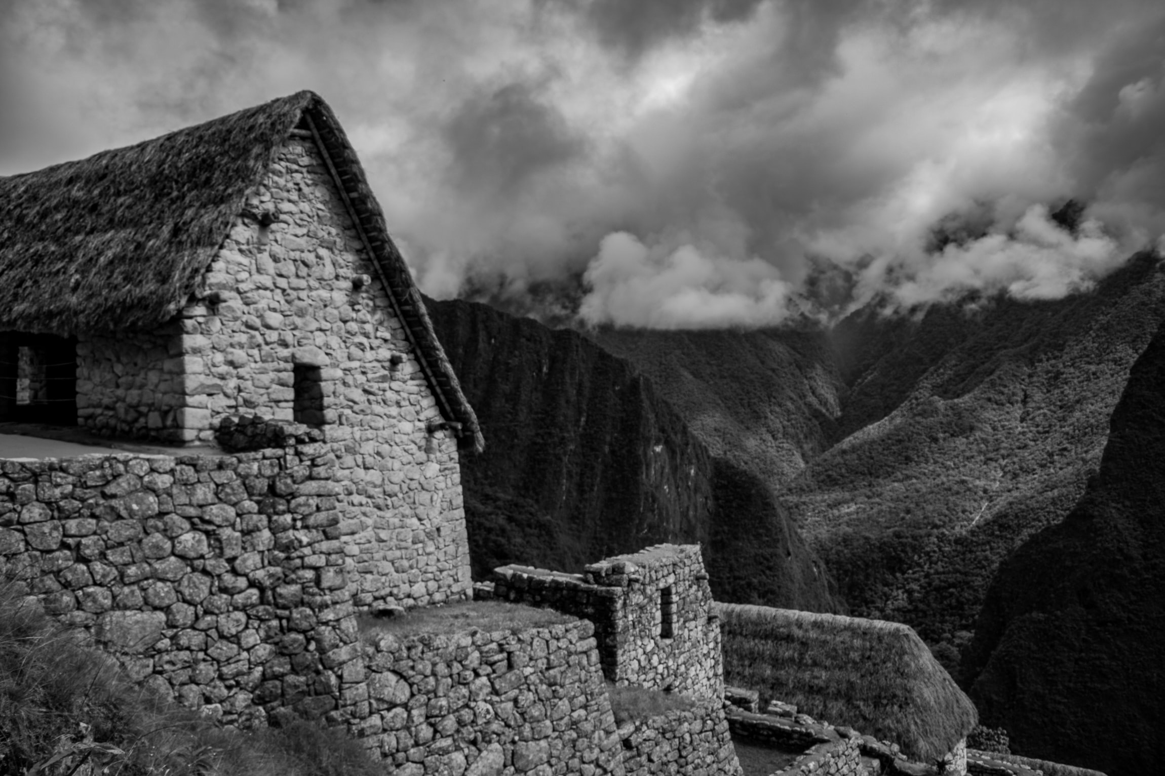 grayscale photography of house near mountain under the cloudy sky