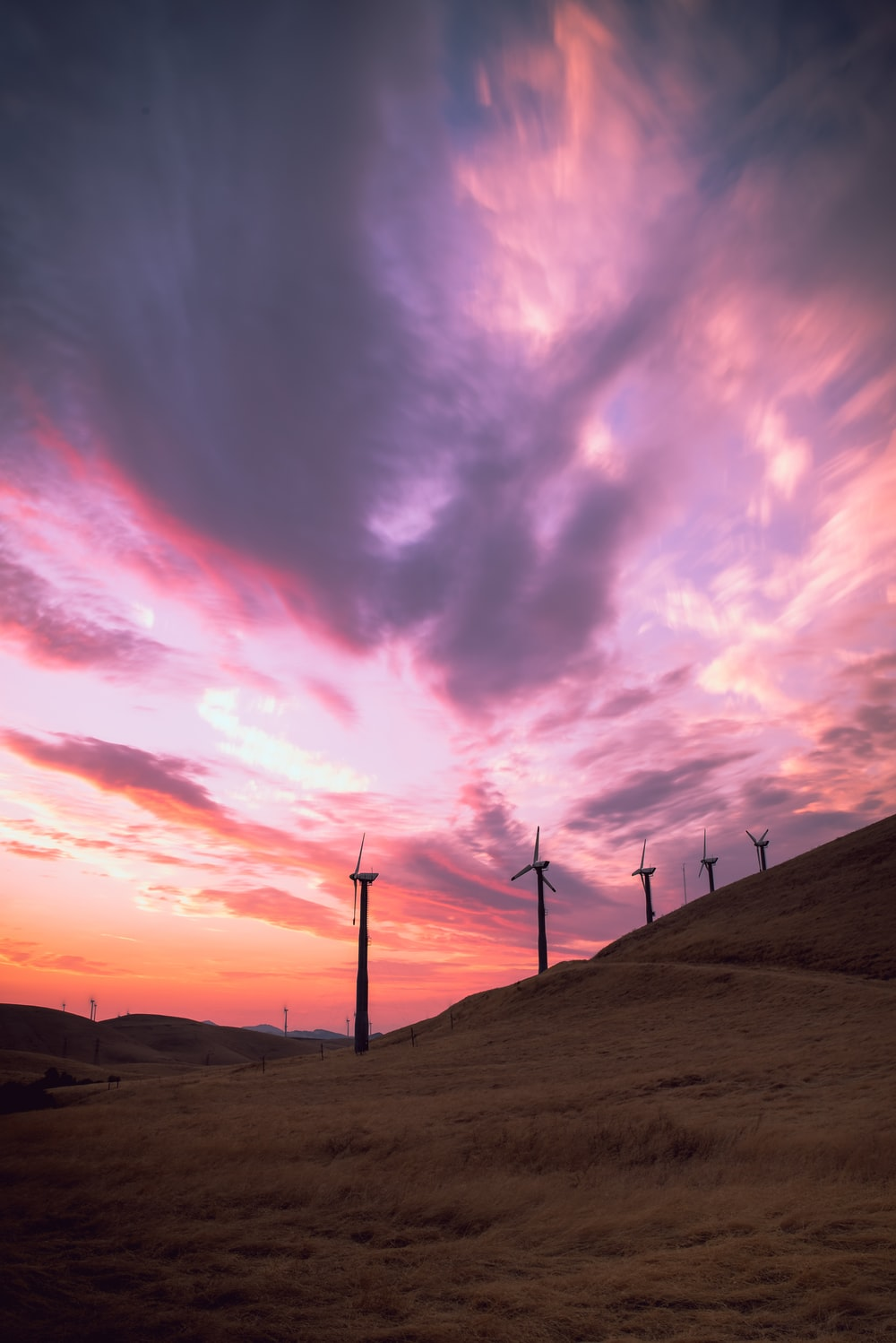 wind mills on hill under cloudy sky