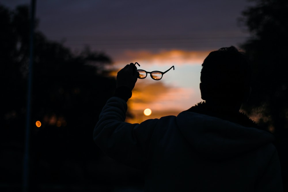 silhouette photo of man holding eyeglasses