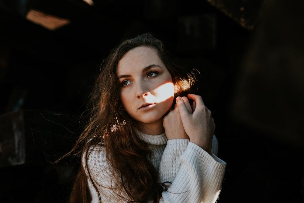woman posing behind dark area during daytime