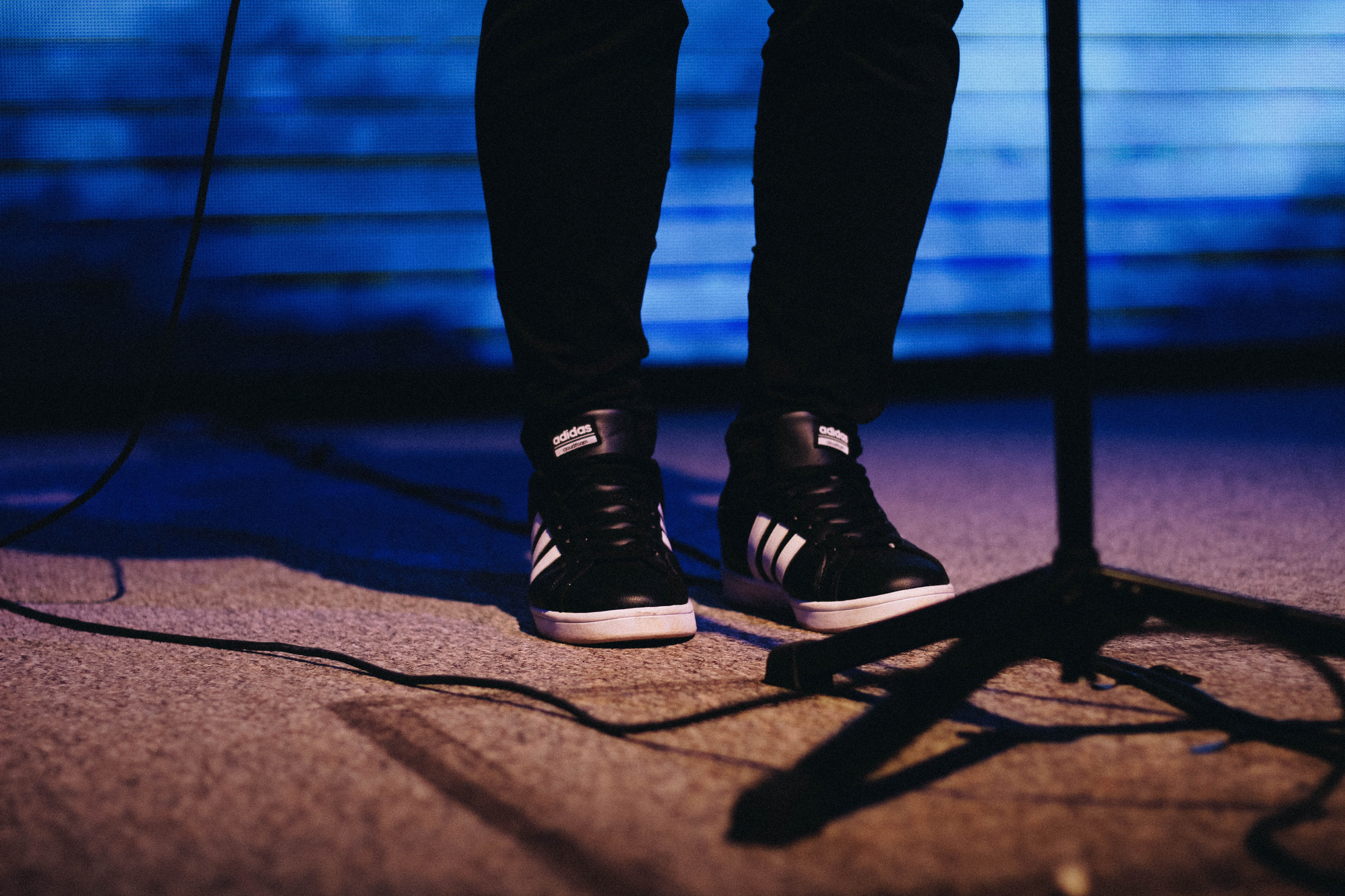 person showing pair of black-and-white adidas shoes