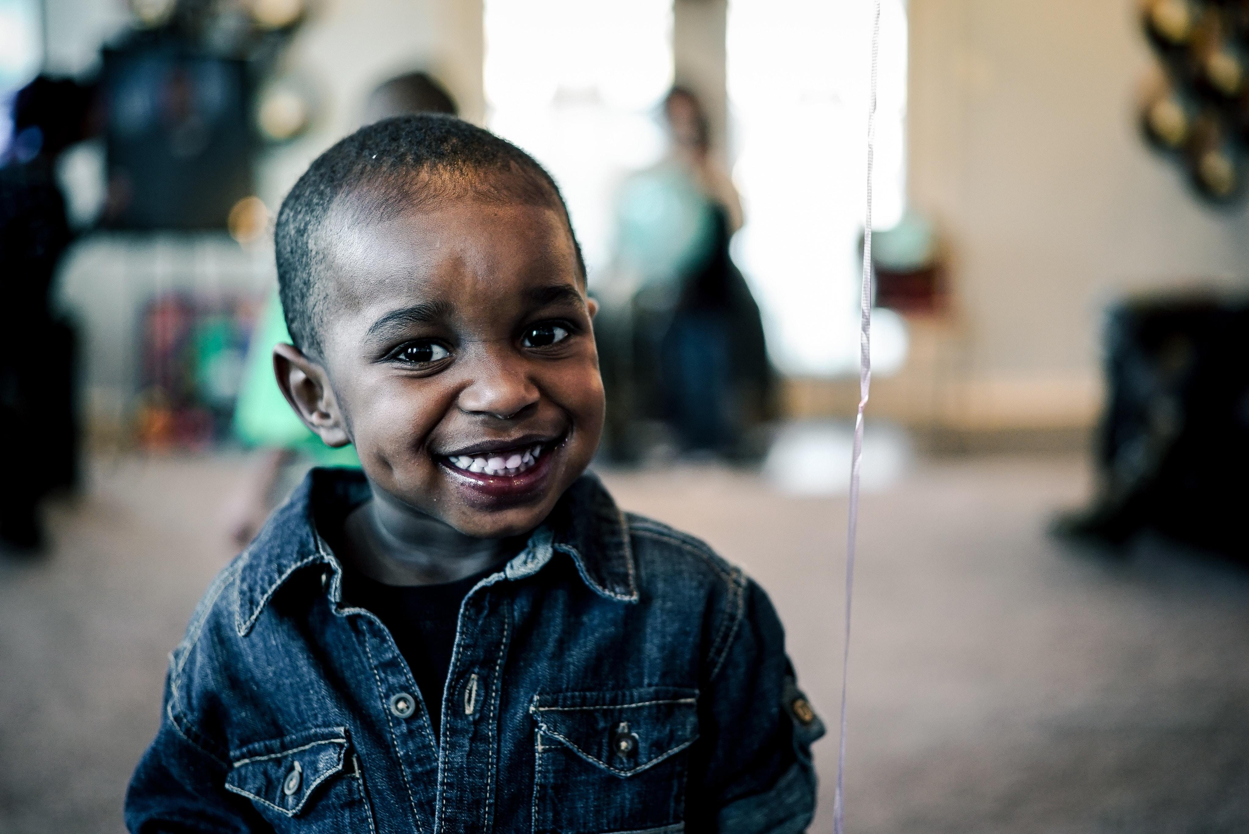 grayscale photo of boy wearing denim jacket smiling near white string